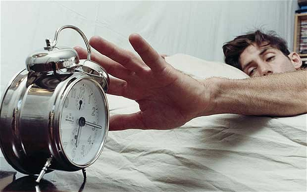 A guy smacking an alarm clock